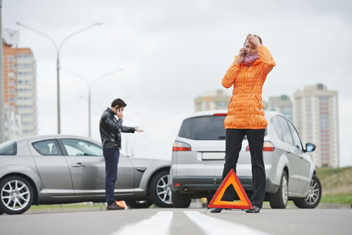 Accident between two cars. You see the warning triangle and the two drivers are talking on the phone.