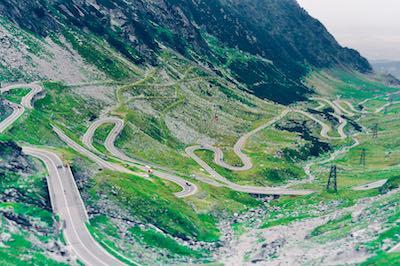 carretera estrecha sin señal pintada en campiña con casa de campo a la derecha