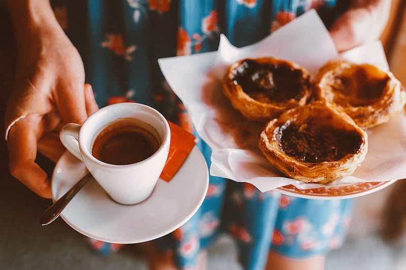 Persona sosteniendo un café y tres dulces típicos portugueses